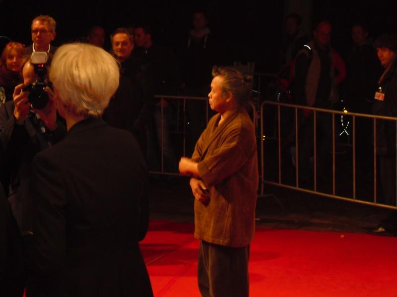 Kim Ki-Duk auf dem roten Teppich; im Hintergrund Laudator Feridun Zaimoglu